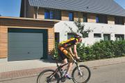 Radfahrer auf Straße vor einem Garagentor
