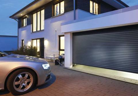 Haus mit sich öffnender Garage und Auto davor